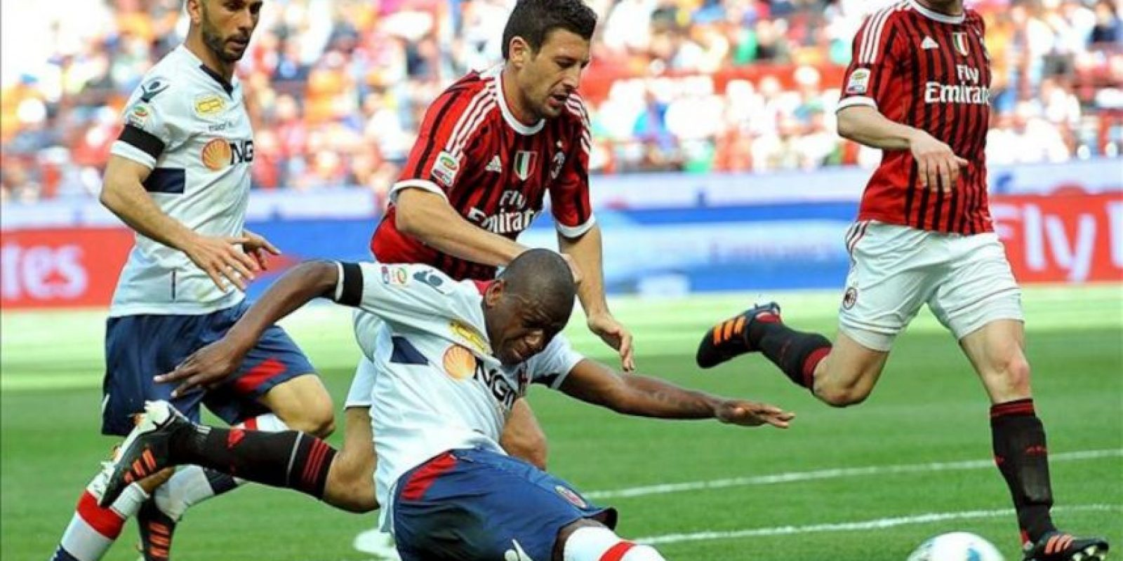 Daniele Bonera (c, detrás), jugador del Milán, intenta evitar el lanzamiento de Gaby Mudingayi (c, delante), del Bolonia, durante el partido de Serie A de la liga italiana de fútbol que enfrentó a sus equipos en el estadio Giuseppe Meazza de Milán, Italia. EFE