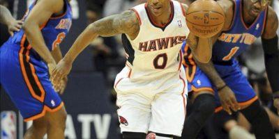 Baron Davis de los New York Knicks (i) intenta hacerse con el control del balón que está en manos de Jeff Teague de los Atlanta Hawks (c) durante la primera mitad del partido de la NBA, disputado en el Philips Arena de Atlanta, Georgia, este 22 de abril. EFE