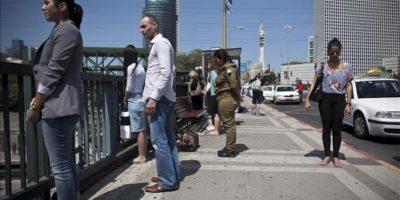 Varios peatones permanecen de pie tras parar por completo su actividad, al igual que la inmensa mayoría de la población israelí y guardar silencio durante dos minutos con el ulular de las sirenas antiaéreas en recuerdo de los seis millones de judíos exterminados por el régimen nazi y sus aliados durante la Segunda Guerra Mundial (1939-1945), en Tel Aviv, Israel, hoy, miércoles 25 de abril de 2012. EFE