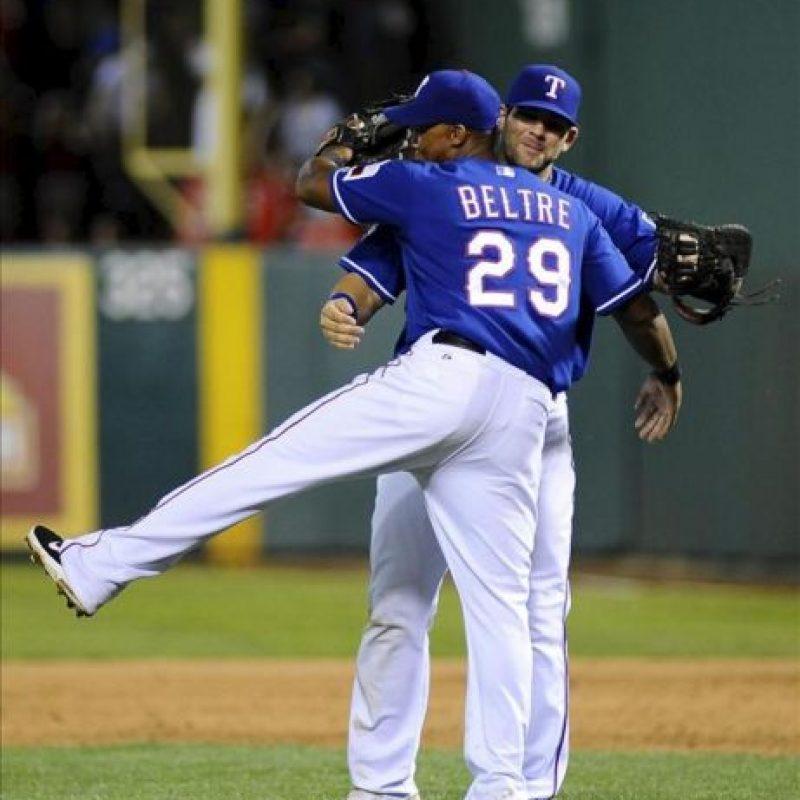 Los Vigilantes de Texas Adrian Beltre (i) y Mitch Moreland (d) celebran su victoria 7-3 ante los Yanquis de Nueva York este miércoles 25 de abril de 2012, durante el juego de la MLB que se disputa en el Rangers Ballpark de Arlington, Texas (EEUU). EFE