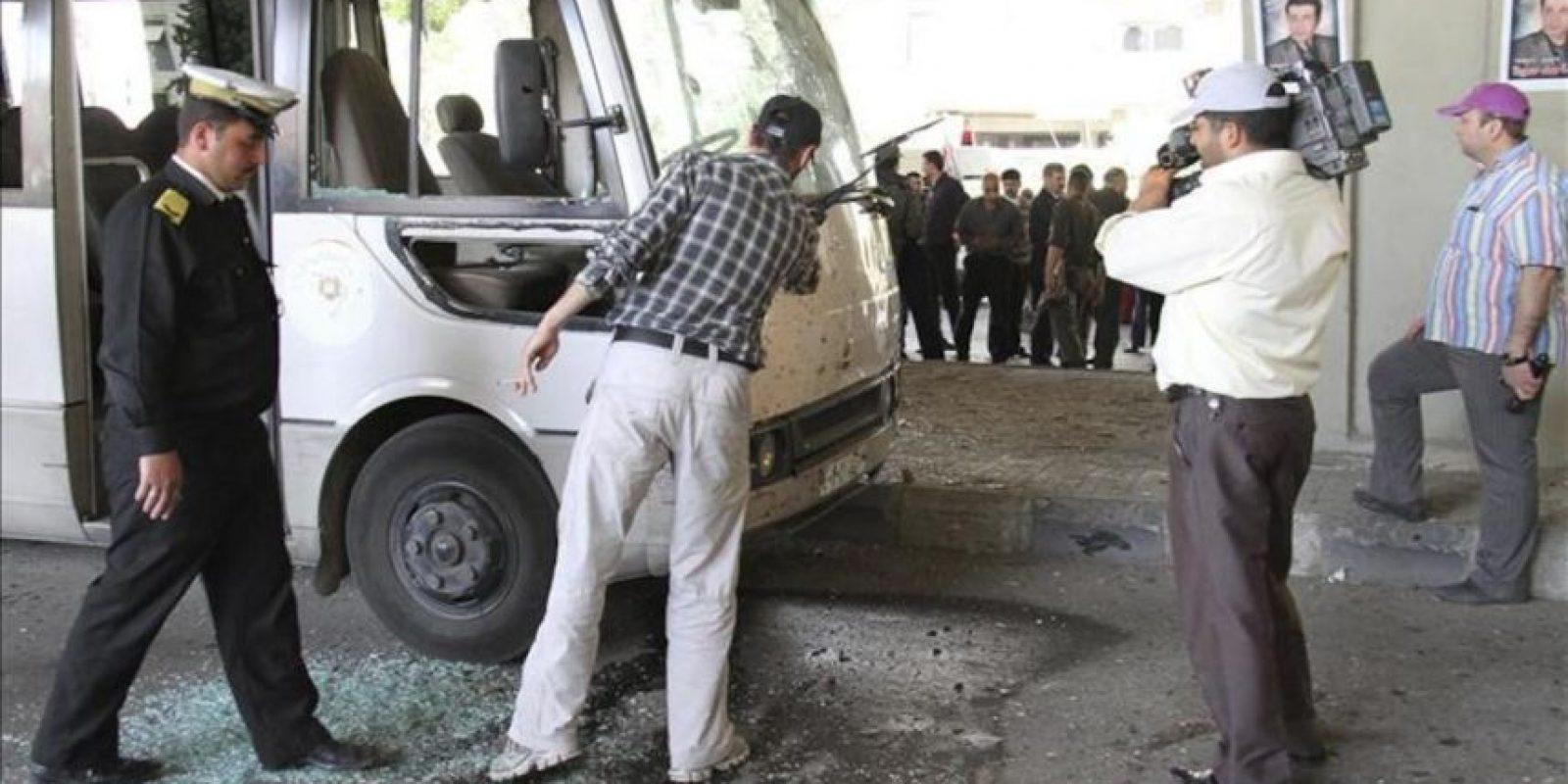 Fotografía facilitada por la agencia de noticias oficial siria, Sana, que muestra a oficiales de la policía inspeccionando un autobús dañado en la escena de una explosión en Damasco (Siria) hoy, viernes, 27 de abril. EFE