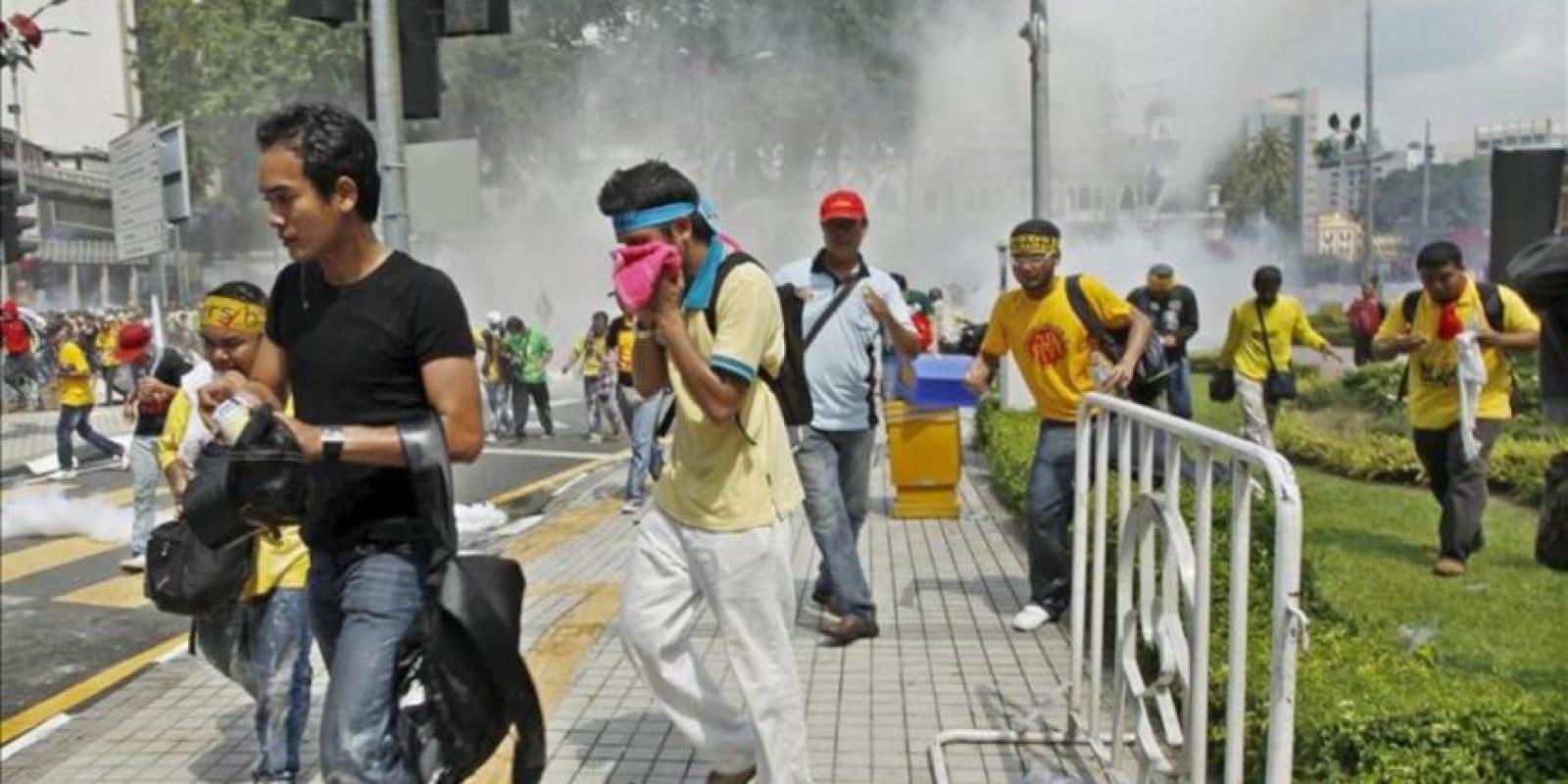 """Manifestantes huyen de una manguera de agua durante una marcha convocada por el colectivo Bersih (""""limpio"""", en malayo) para pedir unas elecciones justas y transparentes hoy en Kuala Lumpur (Malasia). EFE/Ahmad Yusni"""