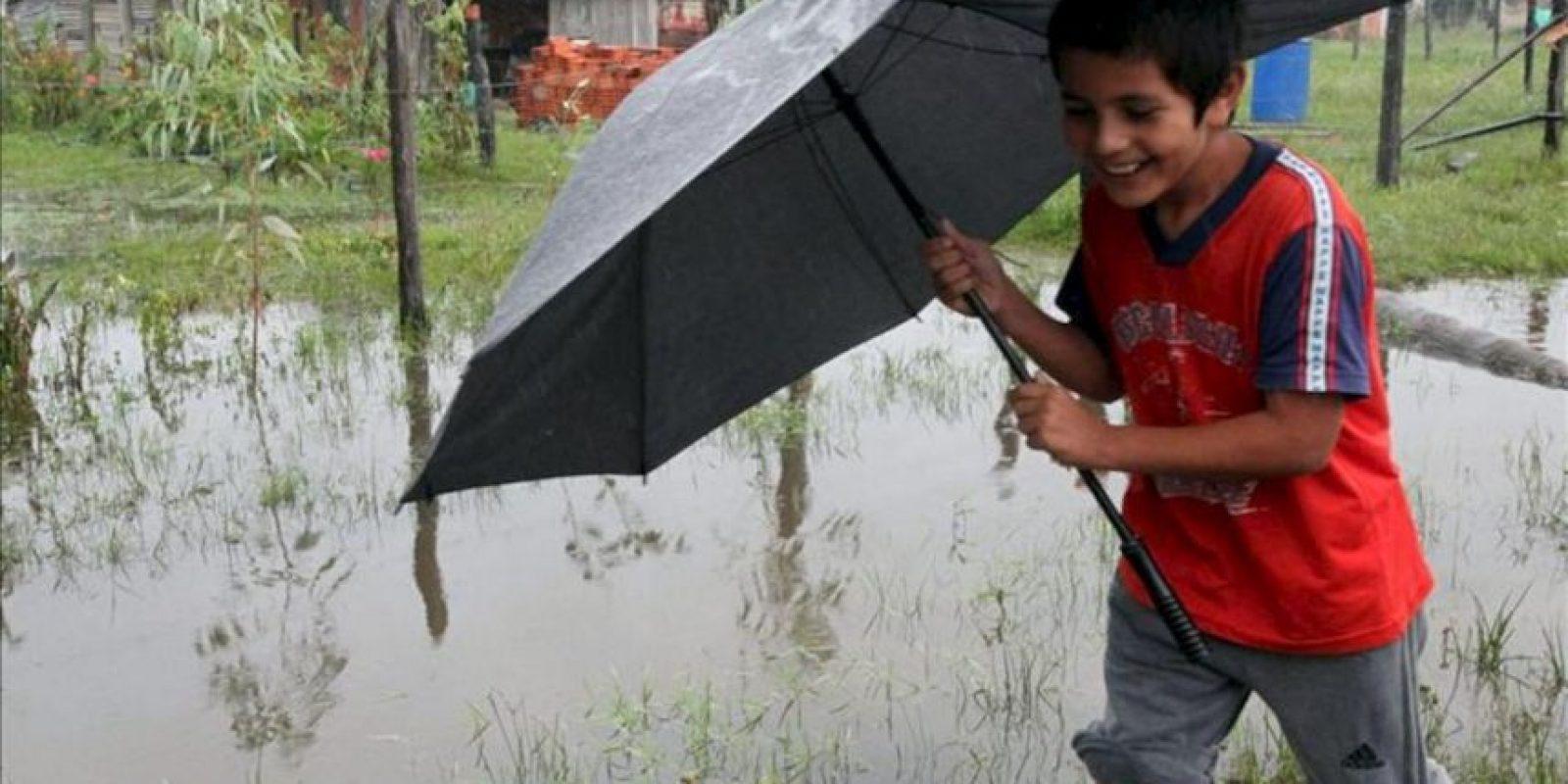 Un joven fue registrado este sábado al caminar por una calle inundada en la localidad de Remansito, a 31 kilómetros de Asunción (Paraguay). EFE