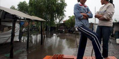 Dos mujeres fueron registradas este sábado al observar desde su casa las inundaciones en la localidad de Remancito, a 31 kilómetros de Asunción (Paraguay). EFE
