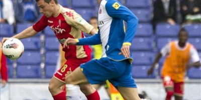 El delantero del Sporting de Gijón Adrián Colunga (i) marca el primer gol de su equipo ante la mirada del defensa del RCD Espanyol Raúl Rodríguez durante el partido, correspondiente a la trigésimo sexta jornada de Liga de Primera División en el estadio Cornellá-El Prat. EFE