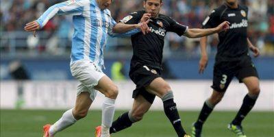 El centrocampista del Málaga CF Joaquín Sánchez (i) conduce el balón ante los jugadores del Valencia CF Jordi Alba (c) y Hedwiges Maduro durante el partido, correspondiente a la trigésimo sexta jornada de la Liga de Primera División, que han disputado ambos equipos en el estadio de La Rosaleda. EFE