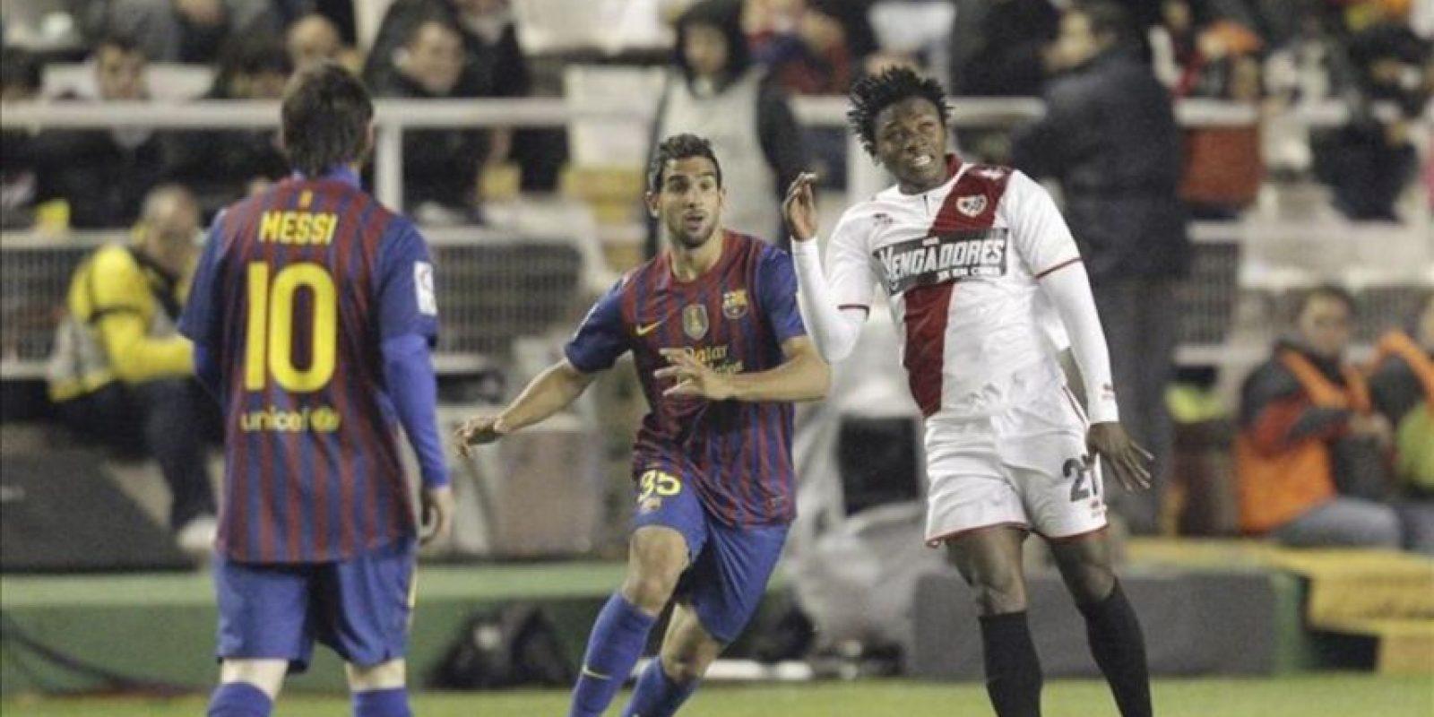 El delantero guineano del Rayo Vallecano Lass Bangoura (d) cabecea un balón ante los jugadores del FC Barcelona Lionel Messi (i) y Martín Montoya durante el partido, correspondiente a la trigésimo sexta jornada de Liga de Primera División en el Estadio de Vallecas. EFE