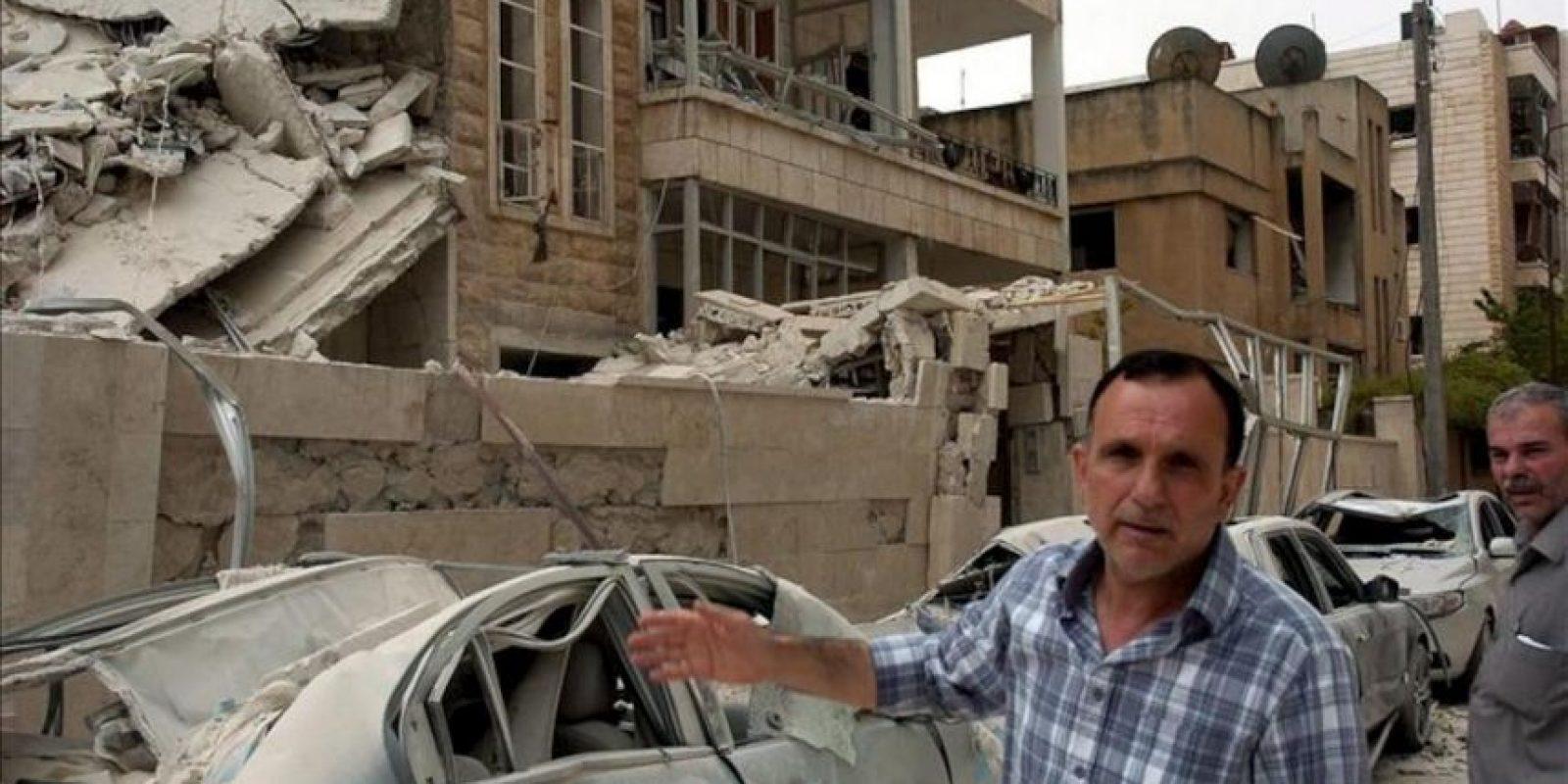 Fotografía distribuida por la Agencia Árabe Siria de Noticias SANA, que muestra a varias personas junto a un edificio afectado por una explosión hoy lunes 30 de abril de 2012 en Idleb, Siria. EFE