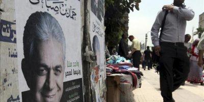Un hombre pasa por delante de una pared cubierta con carteles electorales del candidato Hamdeen Sabahi, en El Cairo, Egipto, hoy. EFE