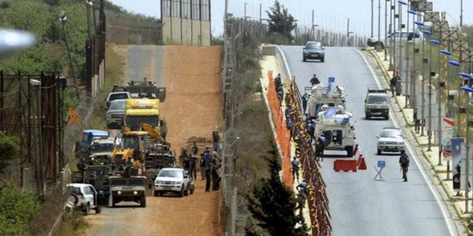 Obreros israelíes (i) retiran una alambrada de espino mientras militares españoles desplazados al Líbano en el marco de la misión UNIFIL de Naciones Unidas patrullan una parte de la frontera entre Líbano e Israel, en la población de Kfar Kila, Líbano, hoy, 30 de abril de 2012. EFE