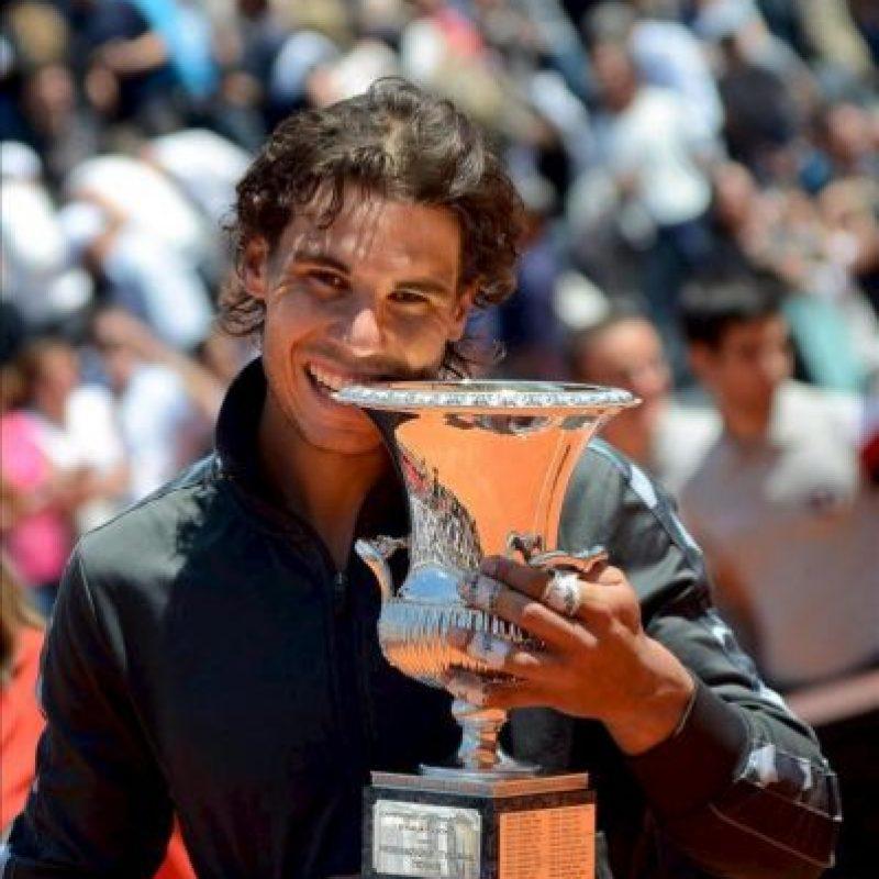 El tenista español Rafa Nadal muerde el trofeo después de proclamarse vencedor del Masters 1000 de Roma en la final que disputó hoy contra el serbio Novak Djokovic en el Foro Itálico de Roma, Italia. Nadal ganó el encuentro por 7-5 y 6-3. EFE