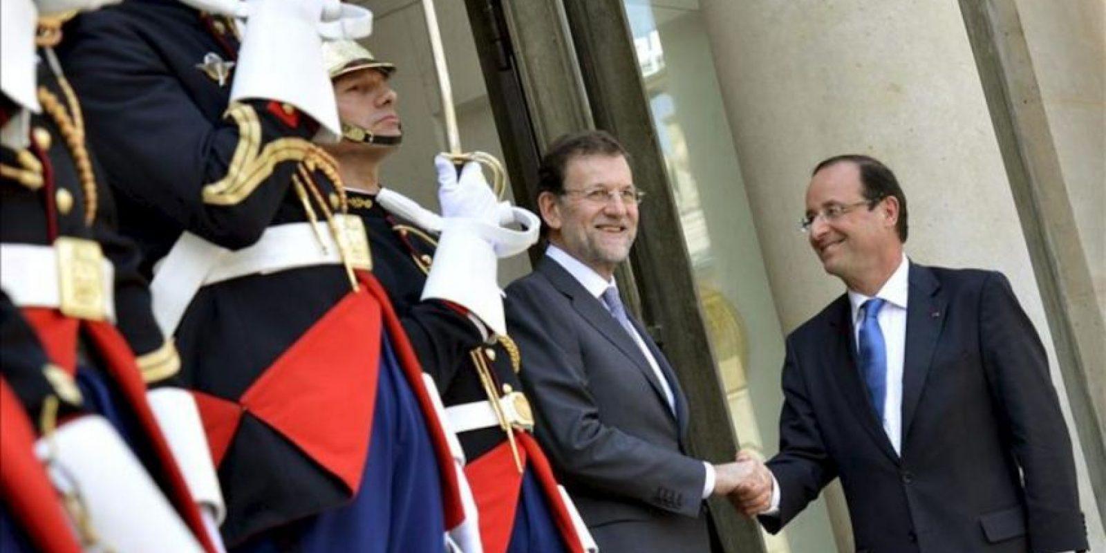 Foto cecida por la presidencia del Gobierno en la que se ve al presidente del Gobierno español, Mariano Rajoy (i), en el momento de ser recibido hoy en el Palacio del Elíseo por el presidente francés, François Hollande. EFE