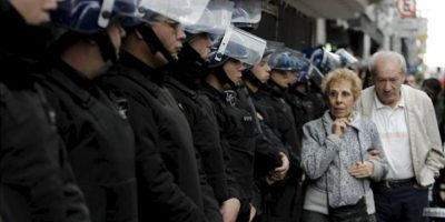Una pareja camina cerca de un grupo de policías que custodiaron este miércoles el Teatro Gran Rex de Buenos Aires (Argentina), donde se realizó un foro con la presentación del expresidente de Colombia Álvaro Uribe. EFE