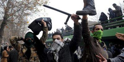 Manifestantes iraníes sostienen una bota, un casco y una porra que supuestamente pertenecen a la policía durante unas protestas contra el presidente iraní Mahmud Ahmadineyad en Teherán, Irán, el 27 de diciembre de 2009. EFE/Archivo