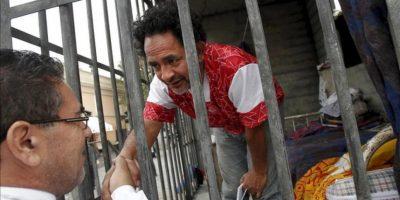 El actor chileno Luis Dubó (d) saluda a un hombre durante su encierro en una celda en el centro de Santiago de Chile (Chile). EFE