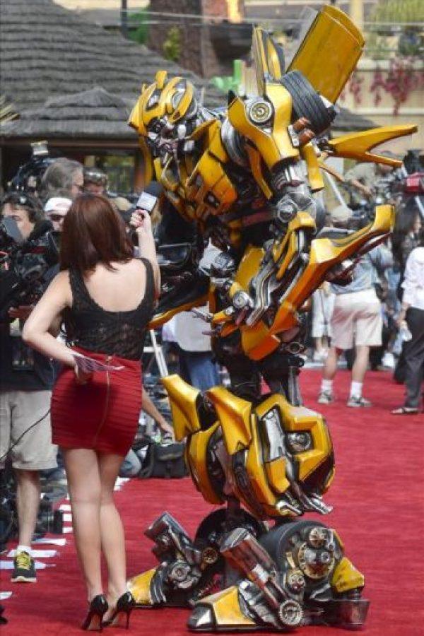 Una reportera de televisión entrevista al personaje Bumblebee (d) en la alfombra roja durante un pase de prensa de 'Transformers: The Ride-3D – The Greatest Battle You'll Ever Ride', en Universal City, de los Estudios de cine Universal, California. EFE