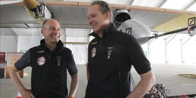 """Los pilotos Andre Borschberg (d), y Bertrand Piccard (i) permanecen junto al avión solar """"Solar Impulse"""", en una carpa del aeropuerto de Barajas. EFE"""