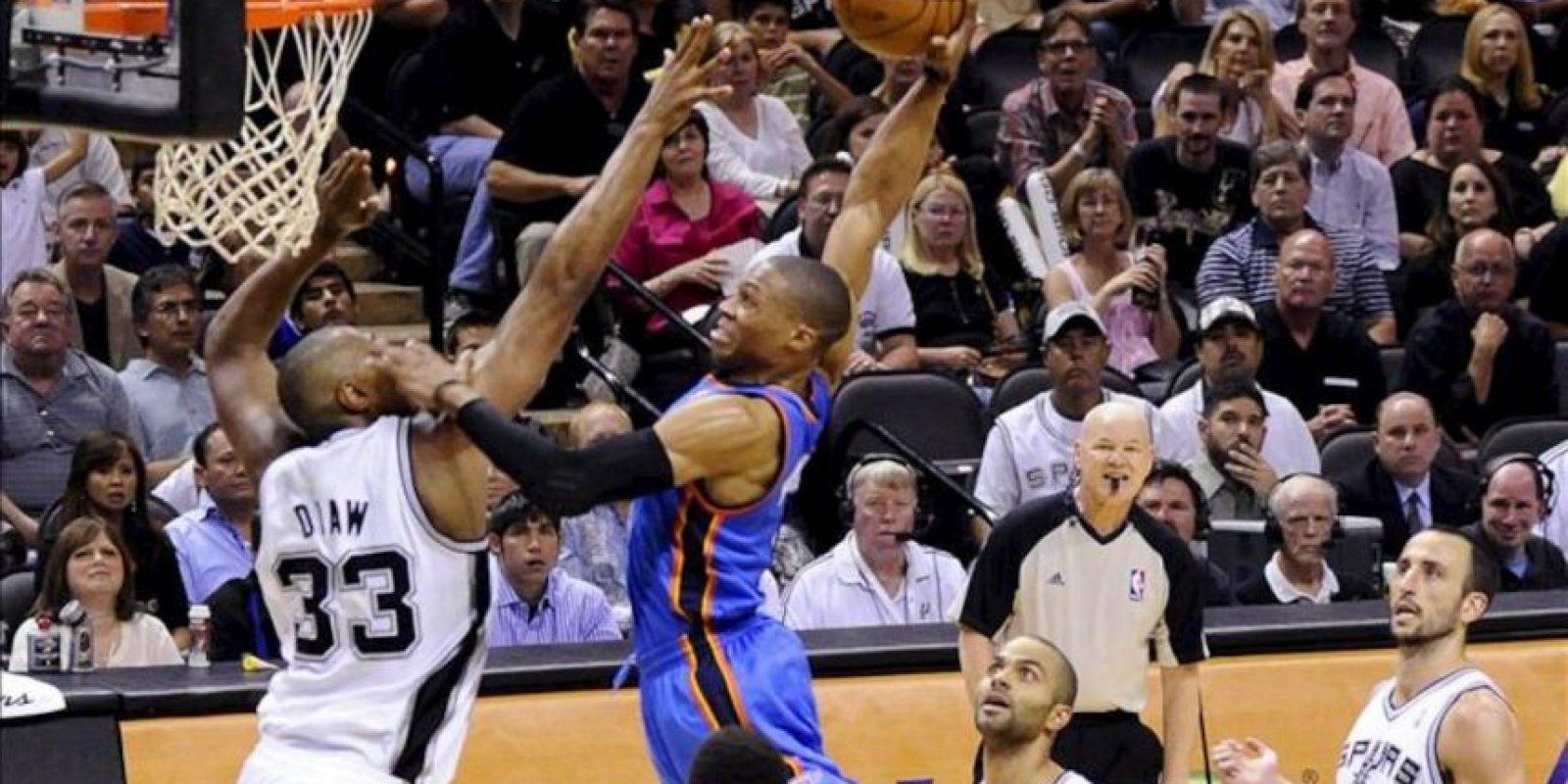El jugador de los Spurs de San Antonio Boris Diaw (i) defiende ante Russell Westbrook (C) de los Thunder de Oklahoma City durante la fase final dentro de la Conferencia Oeste de la NBA que se disputa en el AT&T Center de San Antonio, Texas (EEUU). EFE