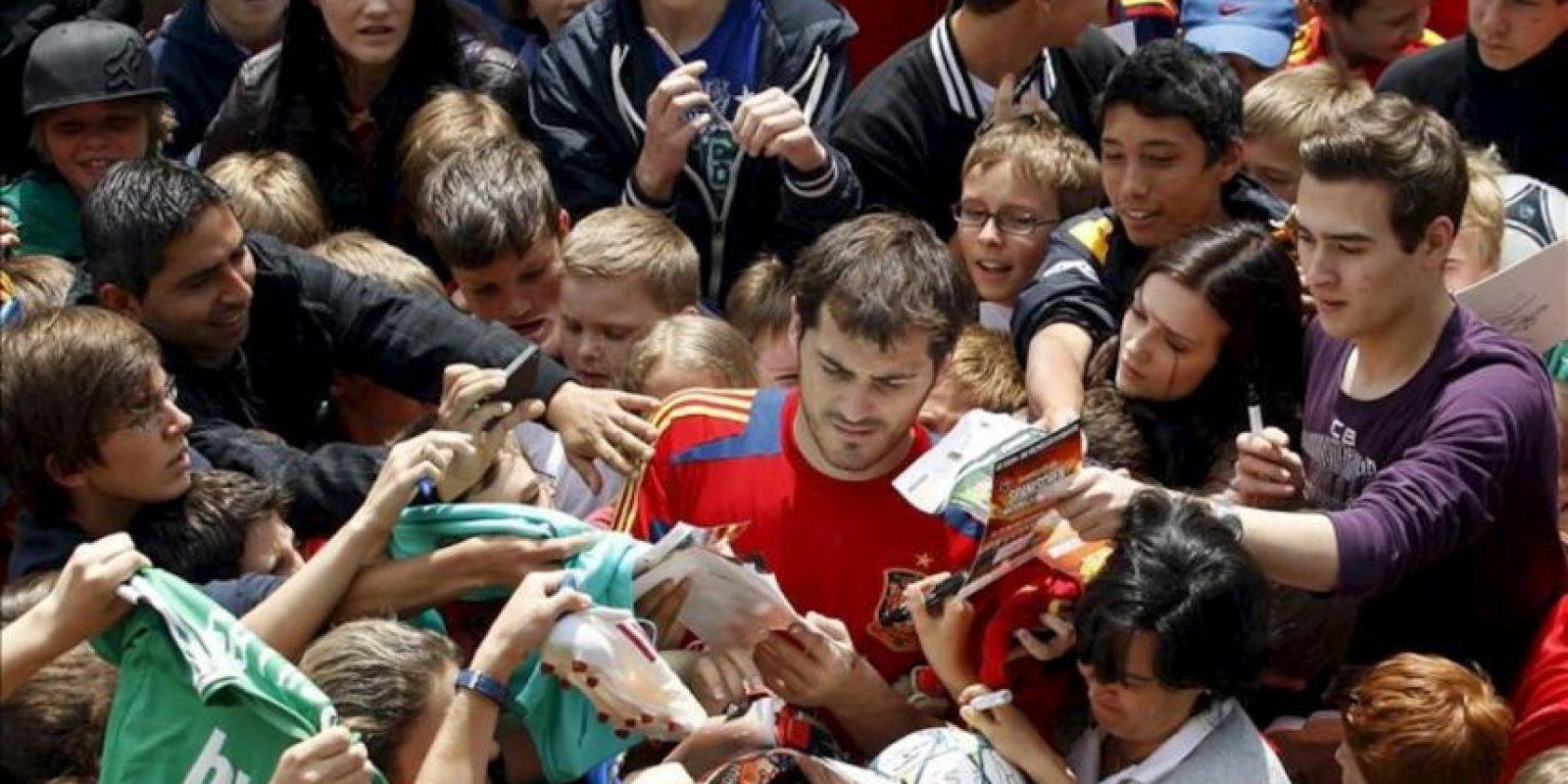 """El guardameta y capitán de la selección española de fútbol Iker Casillas firma autógrafos tras la """"invasión"""" de los aficionados del terreno de juego donde el combinado español entrenó hoy en la localidad austríaca de Schruns dentro de su preparación para la Eurocopa 2012. EFE"""