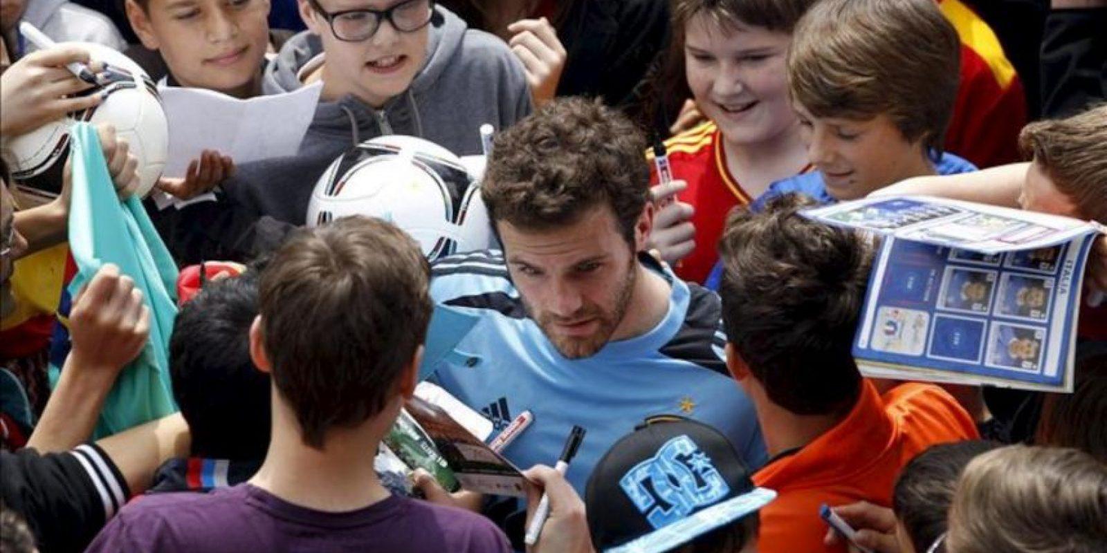 """El jugador de la selección española de fútbol Juan Mata firma autógrafos tras la """"invasión"""" de los aficionados del terreno de juego donde el combinado español entrenó hoy en la localidad austríaca de Schruns dentro de su preparación para la Eurocopa 2012. EFE"""
