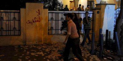 Un grupo de personas camina sobre cientos de papeletas que cubren el suelo a las afueras de la sede del candidato presidencial egipcio Ahmad Shafiq en El Cairo (Egipto). Un grupo de manifestantes ha asaltado y prendido fuego a las oficinas de Shafiq, último primer ministro de Hosni Mubarak. EFE