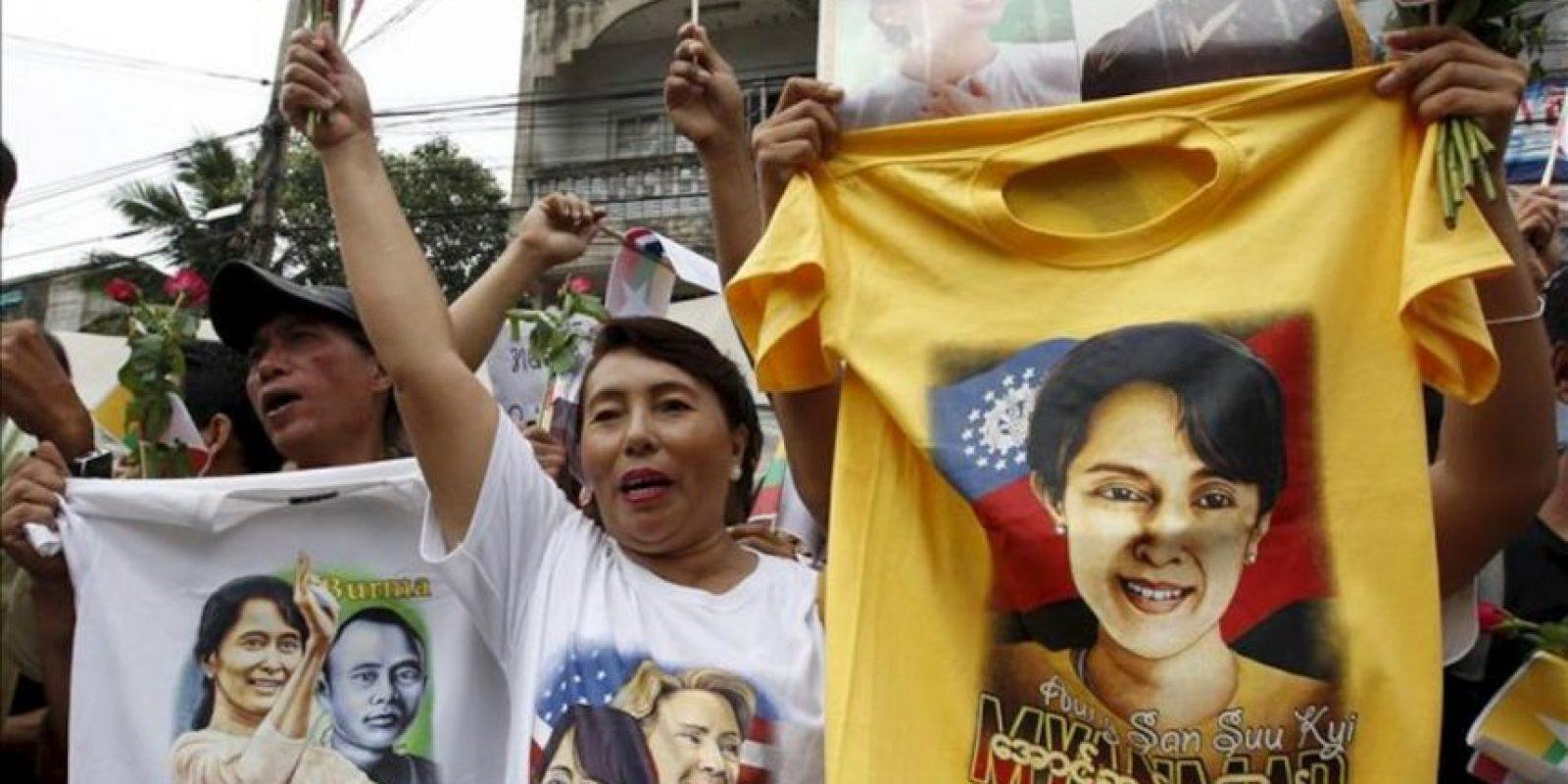 Birmanos muestran camisetas con fotografías de la líder opositora birmana, Aung San Suu Kyi, durante la visita que realizó la Nobel de la paz a un centro de migración birmano en la provincia de Samut Sakhon (Tailandia), en el primer viaje al extranjero que realiza desde 1988. EFE