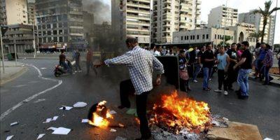Un grupo de libaneses chiíes incendian un contenedor y unos neumáticos en Beirut, en el Líbano, durante una manifestación para exigir la liberación de catorce peregrinos libaneses chiíes que fueron tomados como rehenes por el rebelde Ejército Libre Sirio (ELS) el pasado 22 de mayo. EFE/Archivo