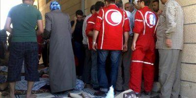 Imagen distribuída por la plataforma de ciudadanos sirios Houla Media Center el 26 de mayo que muestra a trabajadores de Cruz Roja atendiendo a heridos de la masacre de Hula, provincia de Homs, Siria. EFE/Archivo