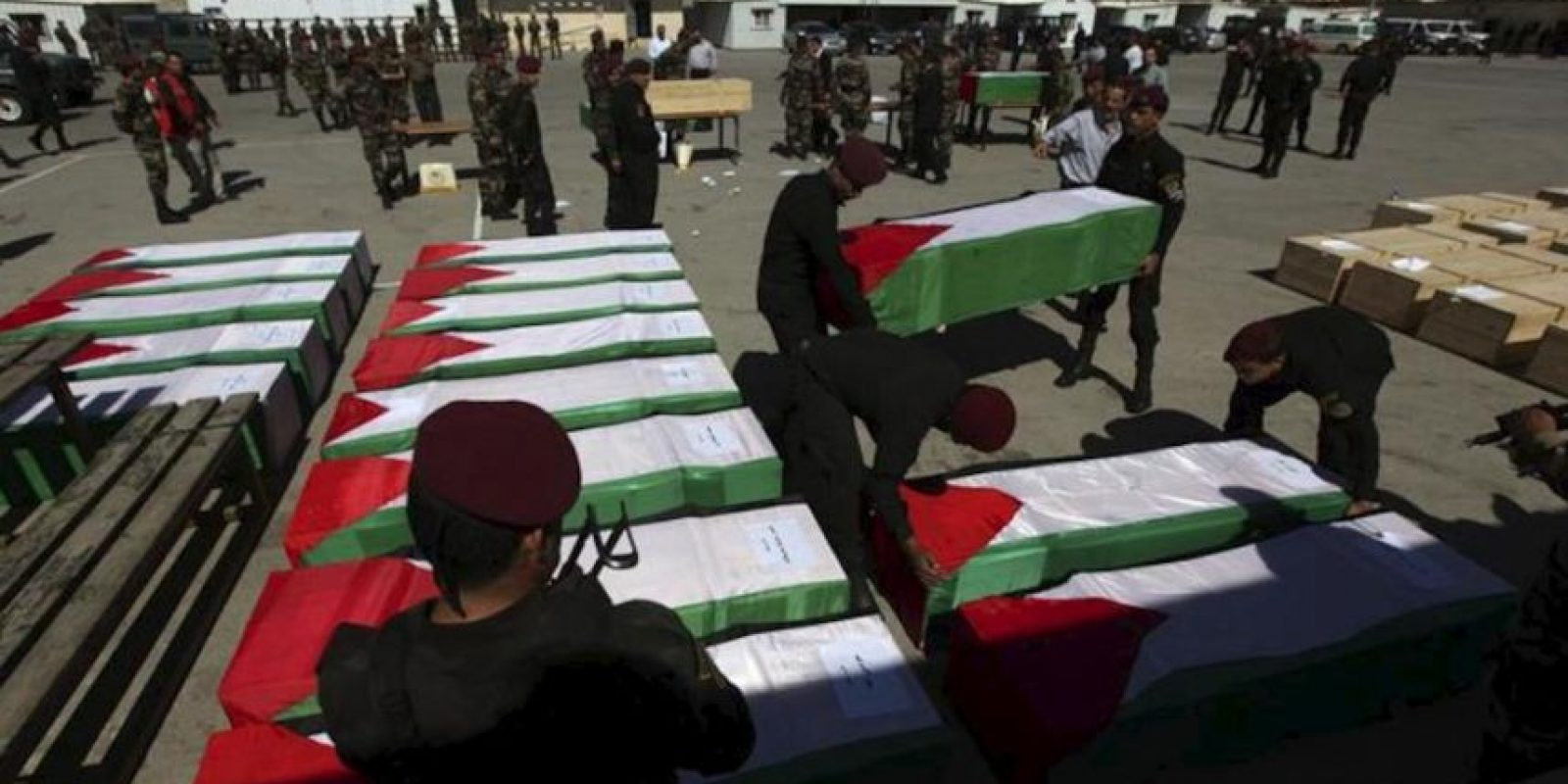Miembros de la seguridad presidencial palestina cargan con uno de los 91 ataúdes de palestinos fallecidos en manos de las fuerzas de seguridad israelíes en los últimos 30 años en Ramala (Cisjordania). EFE
