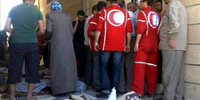 Imagen distribuída por la plataforma de ciudadanos sirios Houla Media Center el 26 de mayo, que muestra a trabajadores de Cruz Roja atendiendo a heridos de la masacre de Hula, en la provincia siria de Homs, registrada el 25 de mayo. EFE