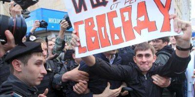 """Unos policías antidisturbios tratan de arrestar a un manifestante que sostiene una pancarta en la que se lee """"Buscando libertad por parte del régimen"""" durante una protesta no autorizada en el centro de Moscú, Rusia, hoy, jueves 31 de mayo. EFE"""