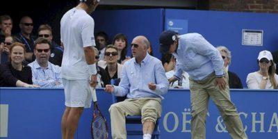 El tenista argentino David Nalbandian (i) observa las lesiones del juez de línea Andrew McDougall (c) en la final del Torneo de Queen's en Londres (Reino Unido). Nalbandian fue descalificado por propinar una patada a la peana de la silla en la que estaba sentado un juez de línea, en el transcurso de la final del torneo de Queen's (Londres), por lo que el título fue para el croata Marin Cilic, sexto cabeza de serie. EFE