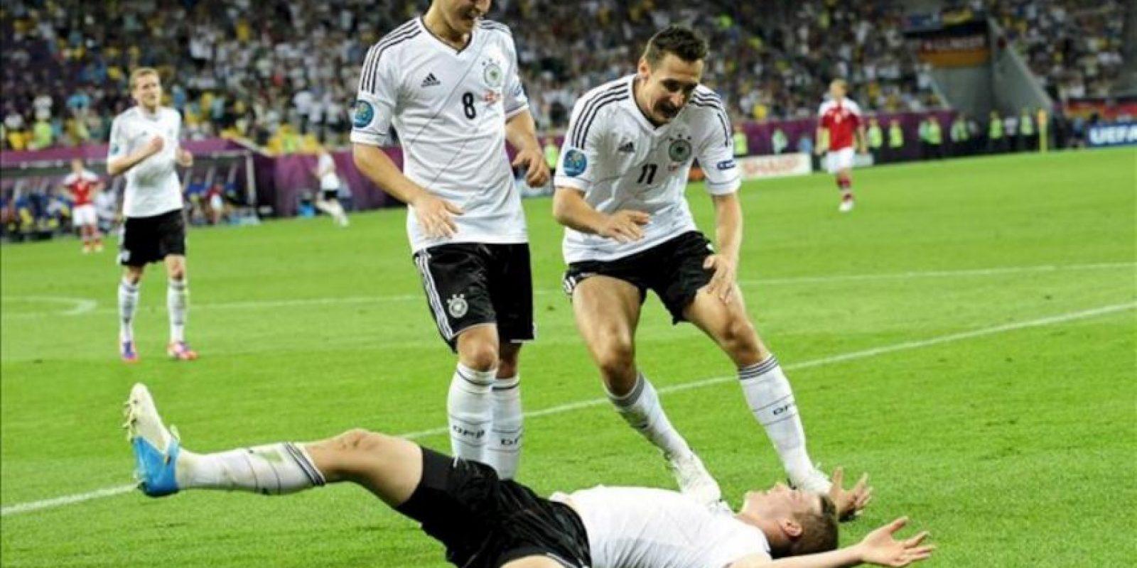 El jugador alemán Lars Bender (abajo) celebra con sus compañeros Mesut Oezil (i) y Miroslav Klose después de anotar contra Dinamarca durante el partido que les enfrentó por el grupo B de la Eurocopa 2012 en Lviv, Ucrania. EFE/GEORGI LICOVSKI