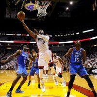 El jugador de Miami Heat Dwyane Wade (c) encesta contra Oklahoma City Thunder durante el tercer juego de la final de la NBA en el American Airlines Arena de Miami, Florida (EE.UU.). EFE