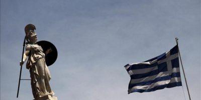 Una bandera griega ondeando al lado de la estatua de la diosa Palas Atenea en el centro de Atenas. EFE/Archivo