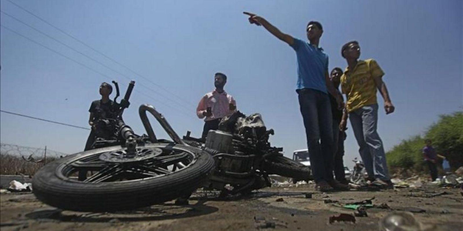 Varios palestinos junto una motocicleta destrozada tras un ataque aéreo del Ejército israelí en la localidad de Beit Hanún, en el norte de Gaza. EFE