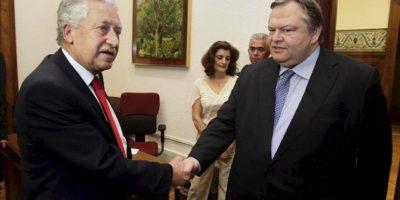 El exministro de Finanzas y líder del socialdemócrata Pasok, Evangelos Venizelos (dcha), estrecha la mano a Fotis Kuvelis, el líder de la formación centroizquierdista Dimar, antes de mantener una reunión en el Parlamento en Atenas (Grecia). EFE