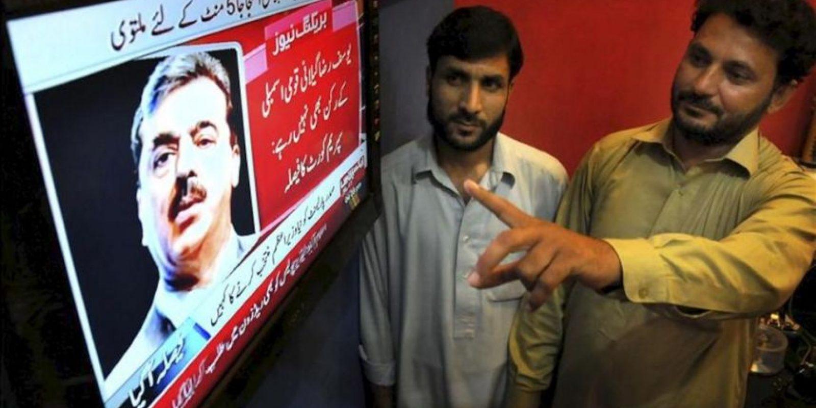 Paquistaníes siguen por televisión la decisión del Tribunal Supremo (TS) de Pakistán de ordenar a la Comisión Electoral del país que inhabilite al primer ministro paquistaní, Yusuf Razá Guilani (en la pantalla). EFE