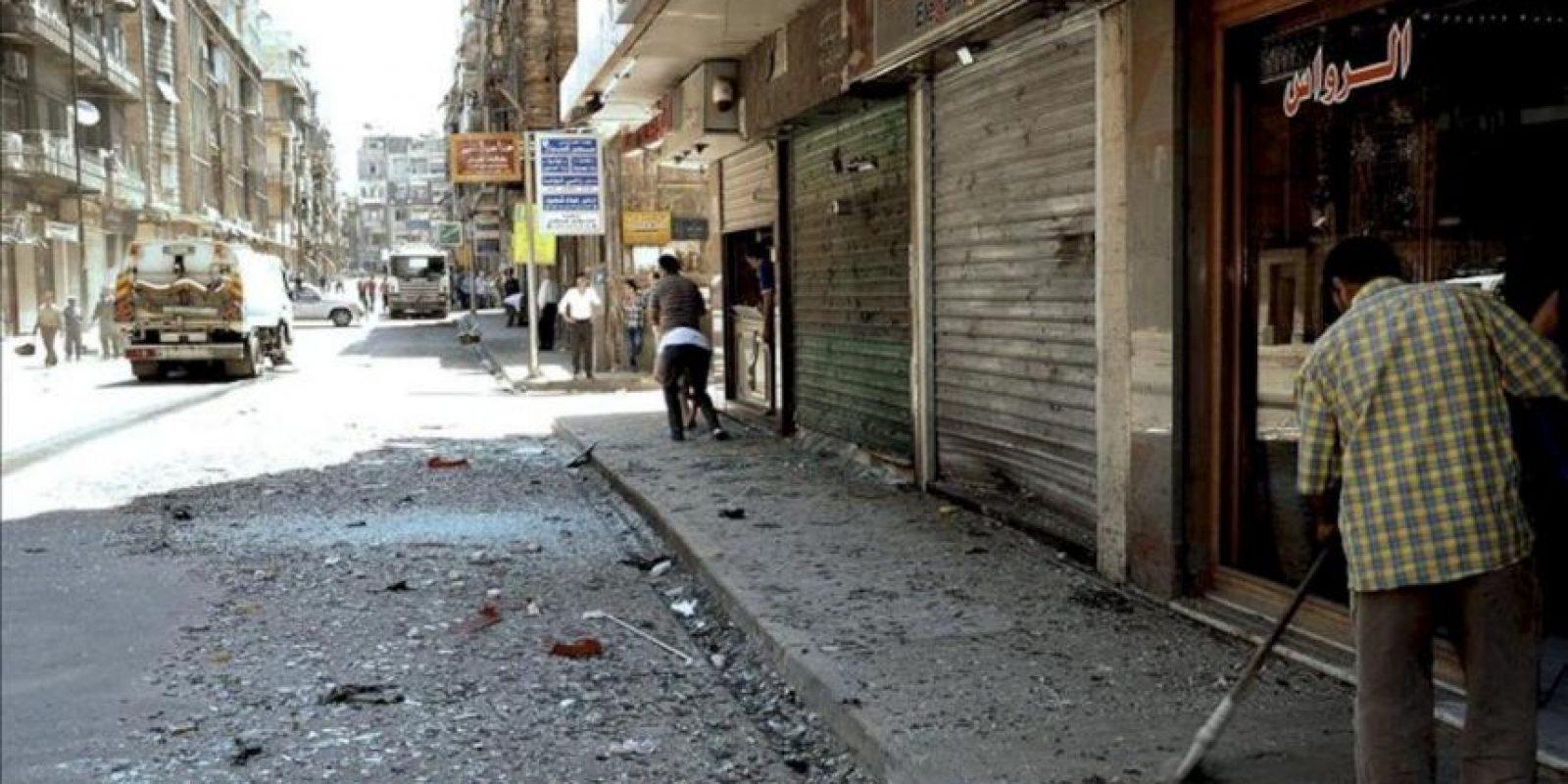 Una fotografía distribuída por la Agencia Árabe de Noticias Siria (SANA) que muestra a un hombre limpiando los escombros junto a su comercio, después de la explosión de una bomba, en en Aleppo, Siria. EFE