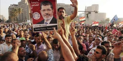 Unos manifestantes sostienen un cartel con el candidato del partido Libertad y Justicia, Mohamed, Morsi, mientras protestan contra el reciente decreto de la Junta Militar gobernante para darse plena potestad y limitar los poderes del futuro presidente de Egipto. EFE