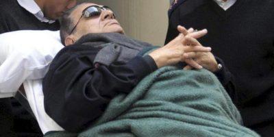 El expresidente egipcio Hosni Mubarak (c) abandona en camilla la sala tras asistir a una nueva sesión de su juicio celebrado en la Academia de Policía en El Cairo (Egipto) el pasado 2 de enero. EFE/Archivo