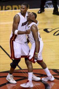 Chris Bosh (i) abraza a su compañero Mario Chalmers (d), de los Heat de Miami, mientras celebran la victoria ante los Thunder de Oklahoma City, tras el cuarto partido de la final de la NBA, en el American Airlines Arena de Miami, Florida (EE.UU.). EFE