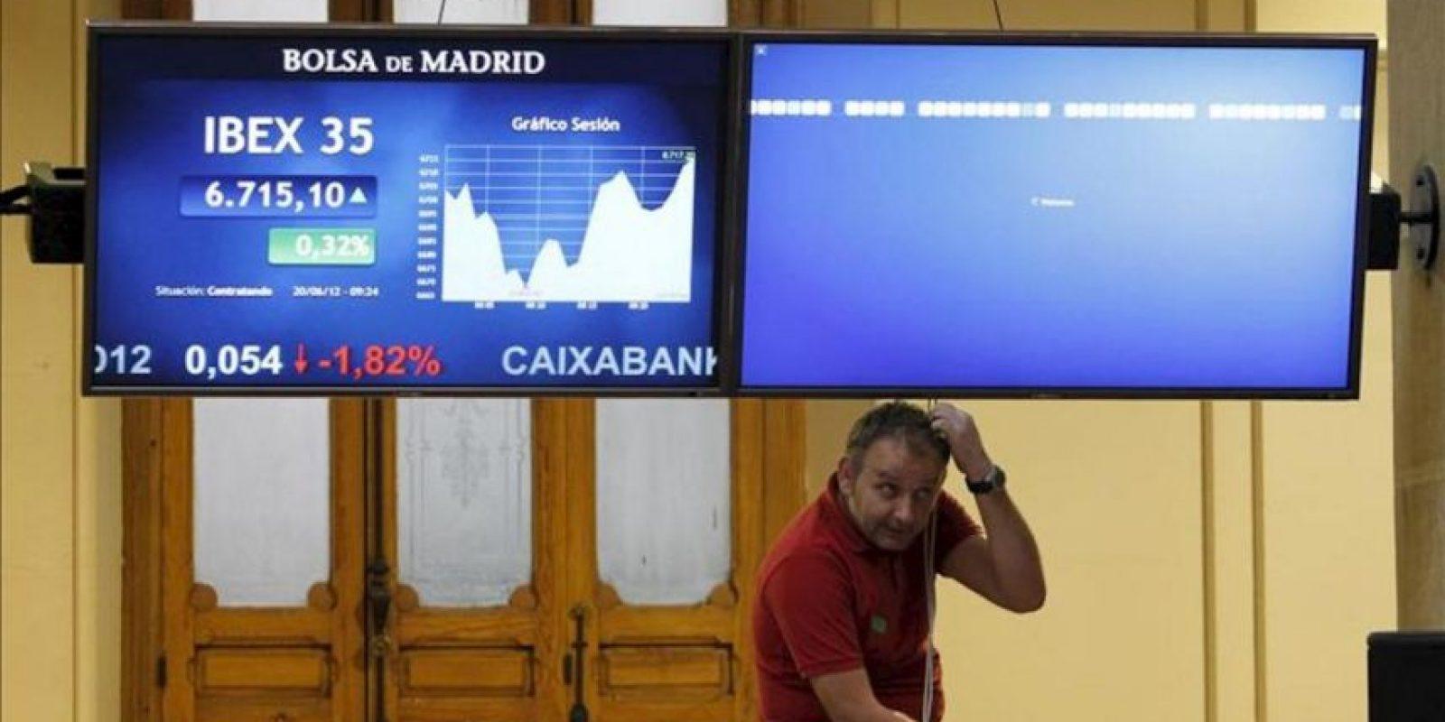 Un técnico arregla uno de los monitores situados en el parqué de Madrid mientras otro muestra la cotización del principal indicador de la Bolsa española, el IBEX 35. EFE