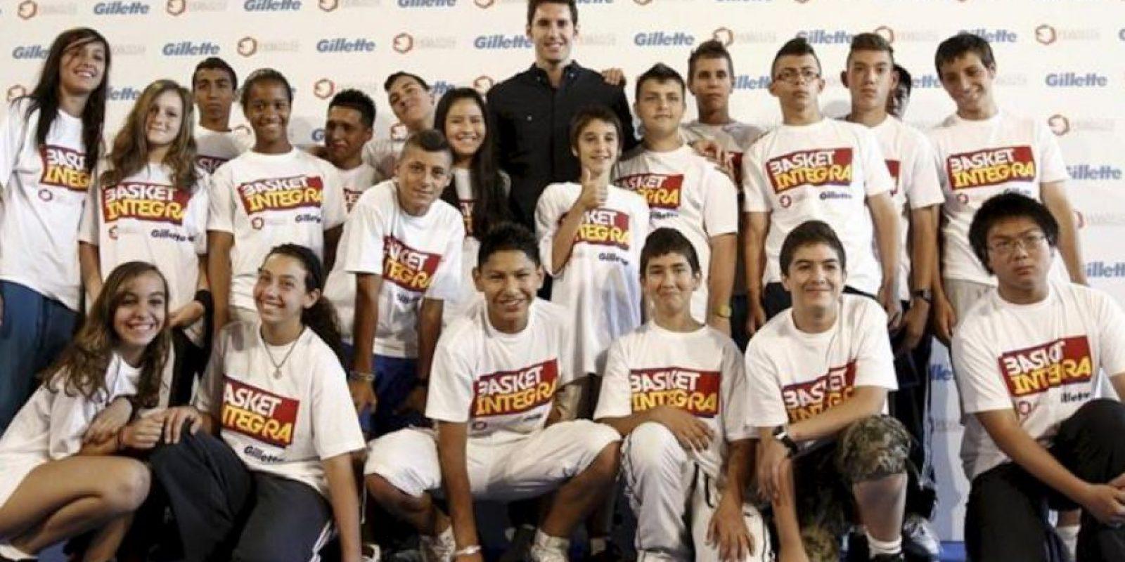 Rudy Fernández, escolta de la selección española y de los Denver Nuggets, posa hoy con un grupo de jóvenes en un acto publicitario dentro de una campaña en ayuda a reducir el índice de absentismo escolar a través del baloncesto. EFE