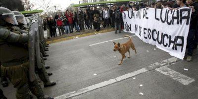 Un grupo de manifestante despliega una pancarta frente a una línea de carabineros, durante una multitudinaria marcha en el centro de Santiago de Chile. EFE