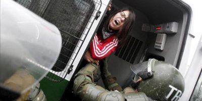 Una mujer es arrestada por carabineros, este 20 de junio, durante una multitudinaria marcha por las calles de Santiago de Chile. EFE