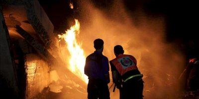 Personal de seguridad del movimiento islamista Hamás intentan controlar el fuego en el complejo destruido de Al Saraya este sábado tras un ataque aéreo israelí en Gaza. EFE