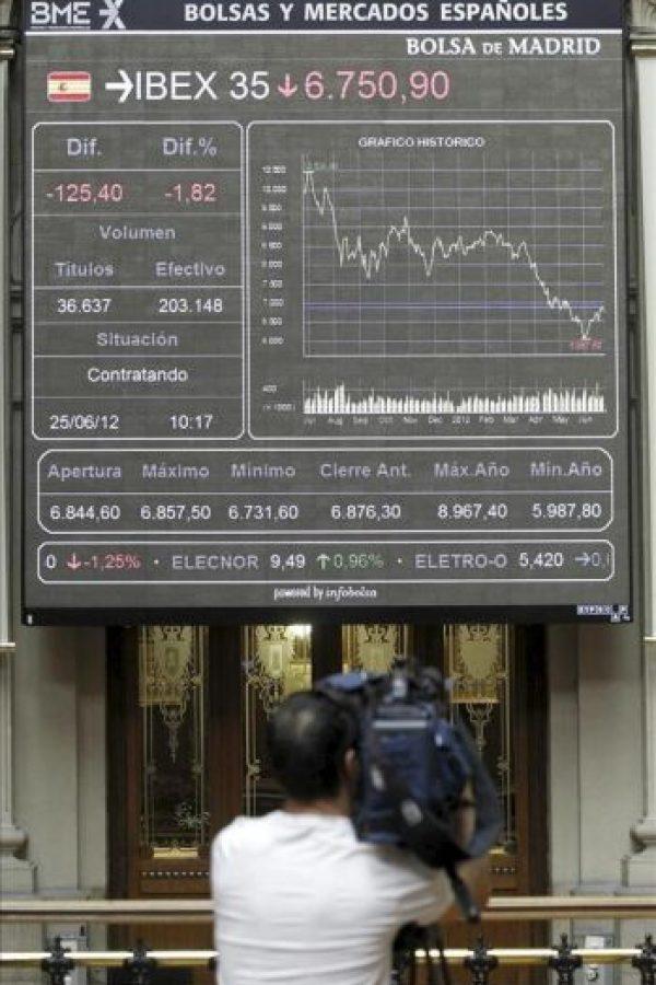 Un reportero toma imágenes del panel situado en la bolsa de Madrid que muestra la cotización del Ibex 35, el principal indicador de la Bolsa española. EFE