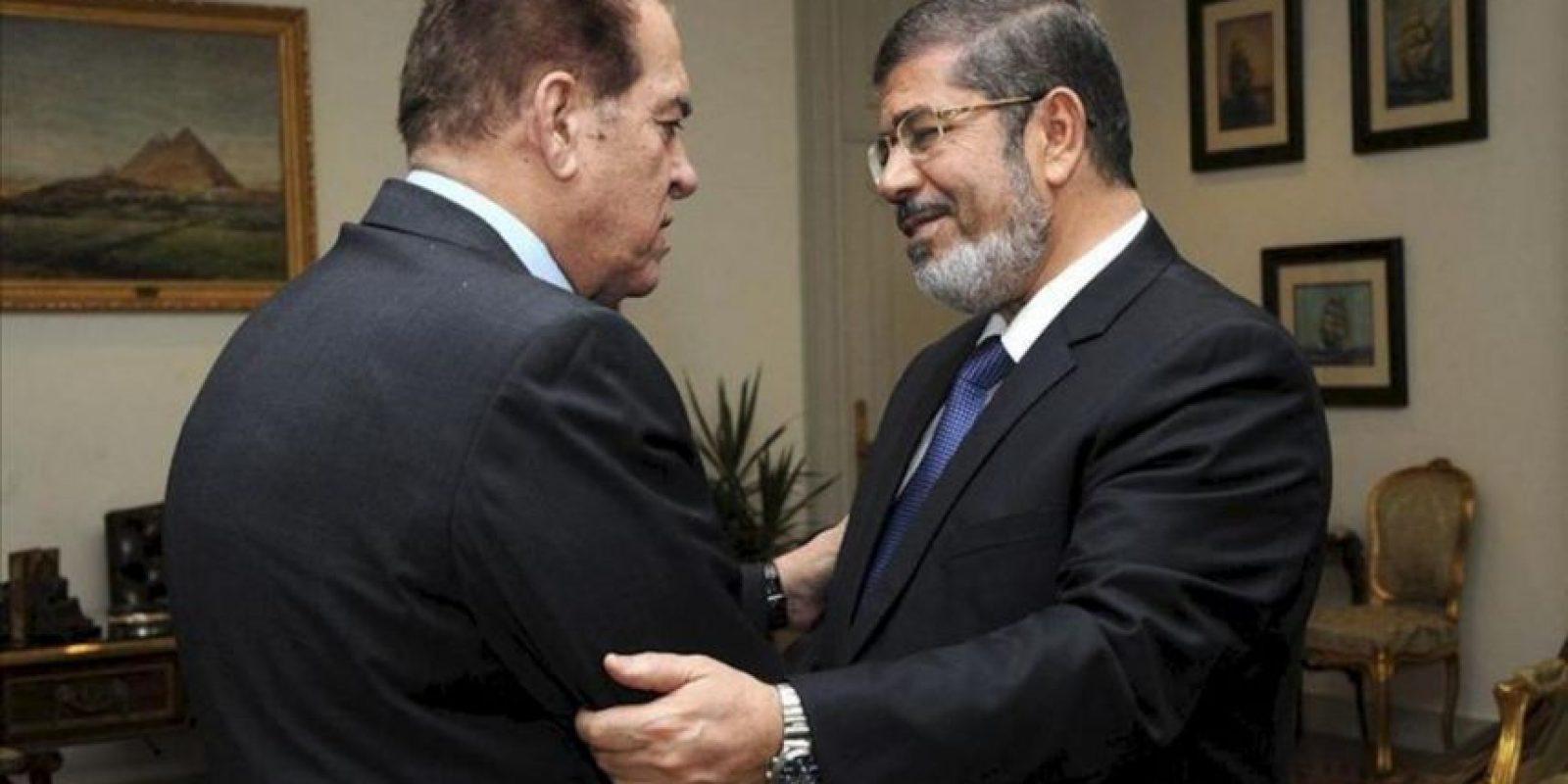 Fotografía distribuída por la Agencia de Noticias de Oriente Medio (MENA), donde muestra al presidente egipcio, Mohamed Morsi (dcha), saludando al primer ministro saliente, Kamal Ganzouri, en su despacho de la Presidencia, en El Cairo, Egipto, el 25 de junio de 2012. El islamista Mohamed Mursi jurará finalmente su cargo ante el Tribunal Constitucional Supremo, según anunció hoy un dirigente de los Hermanos Musulmanes, pese a su intención de hacerlo solo ante el Parlamento, disuelto por una orden de esa corte. EFE
