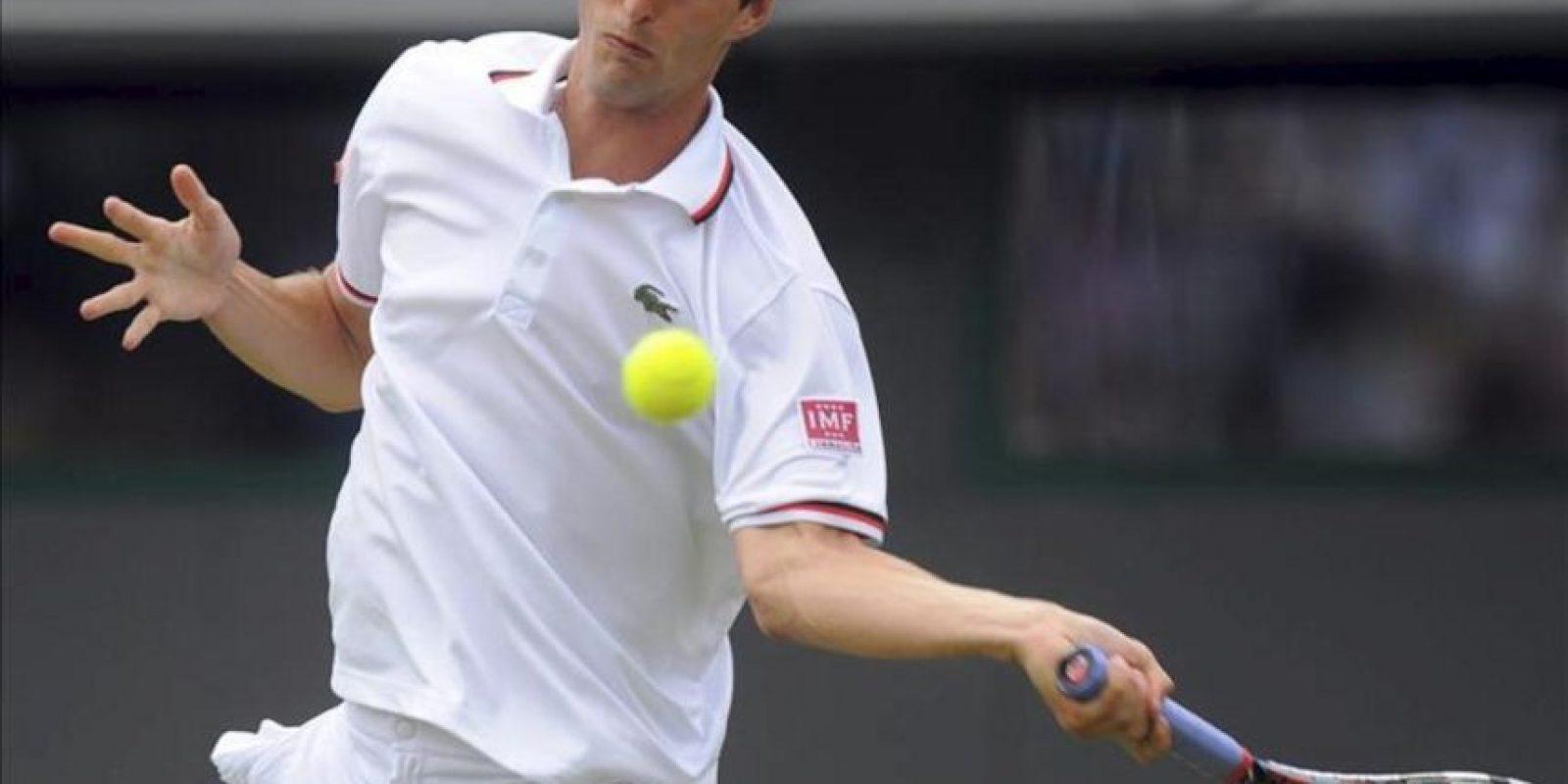 El tenista español Albert Ramos devuelve la pelota al suizo Roger Federer durante su partido de primera ronda del torneo de Wimbledon. EFE